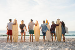 Happy friends standing in line with surfboards Royalty Free Stock Image