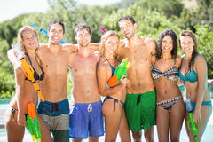 Happy friends standing with water guns Royalty Free Stock Images