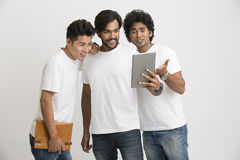 Happy friends surprisingly looking at pc tablet. Group of university friends surprisingly looking at pc tablet on white background royalty free stock images