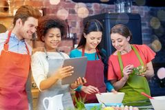 Happy friends with tablet pc cooking in kitchen Stock Photography
