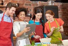 Happy friends with tablet pc cooking in kitchen. Cooking class, friendship, food, technology and people concept - happy friends with tablet pc computer in Royalty Free Stock Images