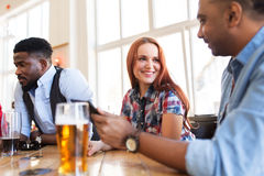 Happy friends with tablet pc drinking beer at bar. Leisure, communication and people concept - group of happy international friends with tablet pc computer Royalty Free Stock Images
