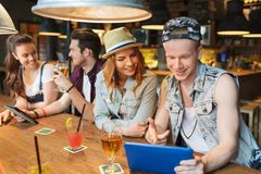 Happy friends with tablet pc and drinks at bar Royalty Free Stock Photos