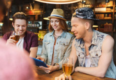 Happy friends with tablet pc and drinks at bar Royalty Free Stock Image