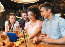 Happy friends with tablet pc and drinks at bar Stock Images