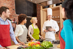 Happy friends with tablet pc in kitchen Royalty Free Stock Images