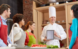 Happy friends with tablet pc in kitchen Stock Photos
