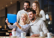 Happy friends with tablet pc taking selfie at cafe. People, leisure, technology and friendship concept - happy friends with tablet pc computer taking selfie at Royalty Free Stock Images