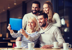Happy friends with tablet pc taking selfie at cafe Royalty Free Stock Images