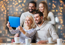 Happy friends with tablet pc taking selfie at cafe Royalty Free Stock Photo
