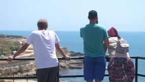 Happy friends taking photo with cellphone on the view point looking on the sea in slow motion. 3840x2160 stock video
