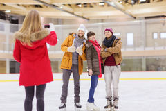 Happy friends taking photo on skating rink Stock Image