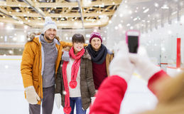 Happy friends taking photo on skating rink Royalty Free Stock Photos