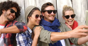 Happy friends taking a selfie. Against wooden background stock video