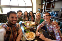 Happy friends taking selfie at bar or pub. People, leisure, friendship and technology concept - happy friends taking selfie, drinking beer and eating snacks at Royalty Free Stock Photos