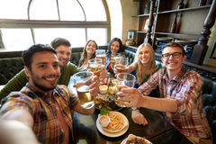 Happy friends taking selfie at bar or pub. People, leisure, friendship and technology concept - happy friends taking selfie, drinking beer and eating snacks at Royalty Free Stock Image