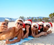 Happy friends taking selfie on beach on christmas stock image