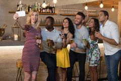 Happy friends taking selfie while having drinks Royalty Free Stock Photo