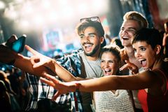 Happy friends taking selfie at music festival Royalty Free Stock Image