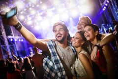 Happy friends taking selfie at music festival. Happy young friends taking selfie at music festival royalty free stock image