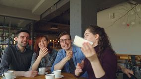 Happy friends are taking selfie in pizza house, making funny faces and gestures and laughing then watching pictures stock footage