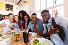 Happy friends taking selfie at restaurant or bar. Leisure, friendship, people and holidays concept - happy friends taking selfie at restaurant or bar royalty free stock images