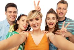 Happy friends taking selfie and showing peace royalty free stock images