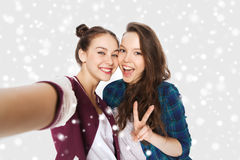Happy friends taking selfie and showing peace. Winter, christmas, people, teens and friendship concept - happy smiling pretty teenage girls or friends taking Stock Image
