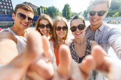 Happy friends taking selfie and showing thumbs up Royalty Free Stock Photography