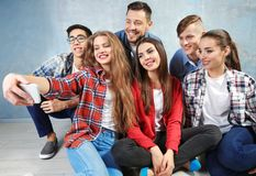 Happy friends taking selfie while sitting on floor Stock Photography