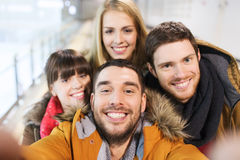 Happy friends taking selfie on skating rink Royalty Free Stock Photography