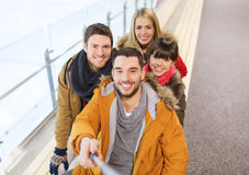 Happy friends taking selfie on skating rink Royalty Free Stock Images