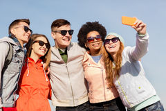 Happy friends taking selfie by smartphone outdoors Royalty Free Stock Images