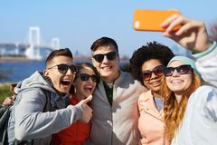 Happy friends taking selfie with smartphone Royalty Free Stock Images