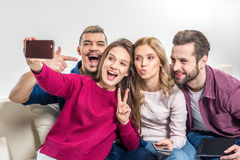 Happy friends taking selfie. Happy young friends taking selfie while sitting on couch Royalty Free Stock Images