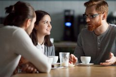 Happy friends talk having coffee hanging together in cafe. Diverse friends meeting in coffeeshop talking at table, happy students have fun in cafe enjoying royalty free stock images
