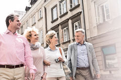 Happy friends talking while walking in city Stock Photography