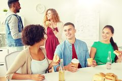 Happy friends or team eating at office royalty free stock images