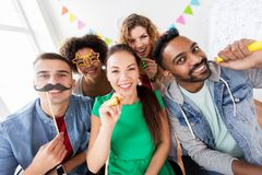 Happy friends or team having fun at office party Stock Photos