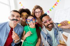 Happy friends or team having fun at office party. Corporate, celebration and holidays concept - happy friends or team with party accessories having fun at office royalty free stock photos