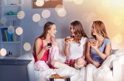 Happy friends or teen girls eating pizza at home. Friendship, people, pajama party, entertainment and junk food concept - happy friends or teenage girls eating Stock Images