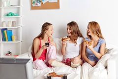 Happy friends or teen girls eating pizza at home. Friendship, people, pajama party, entertainment and junk food concept - happy friends or teenage girls eating Royalty Free Stock Image