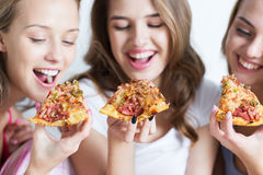 Happy friends or teen girls eating pizza at home Royalty Free Stock Photography