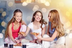 Happy friends or teen girls eating pizza at home. Friendship, people, pajama party and junk food concept - happy friends or teenage girls eating pizza at home Stock Image