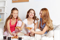 Happy friends or teen girls eating pizza at home. Friendship, people, pajama party and junk food concept - happy friends or teenage girls eating pizza at home Royalty Free Stock Images