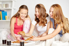 Happy friends or teen girls eating pizza at home. Friendship, people, pajama party and junk food concept - happy friends or teenage girls eating pizza at home Royalty Free Stock Image