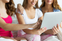 Happy friends or teen girls with tablet pc at home Royalty Free Stock Photo