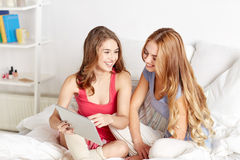 Happy friends or teen girls with tablet pc at home Stock Photography