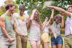 Happy friends throwing powder paint Stock Photos