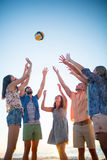 Happy friends throwing volleyball Royalty Free Stock Image